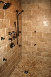 Walk-in shower with multiple shower heads and tan tile